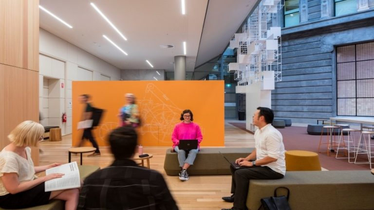A young woman in a pink jumper sits in the StartSpace coworking area typing on a laptop, while other people move around her