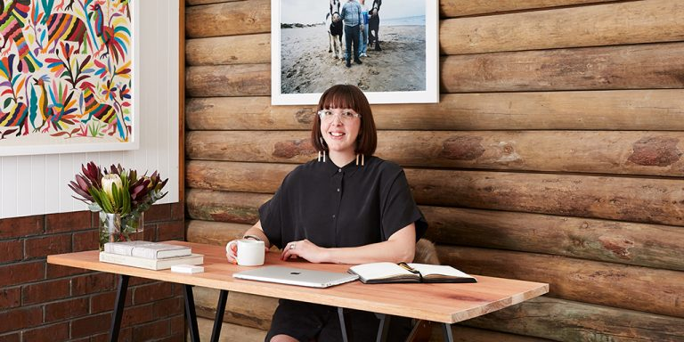 Fiona Killackey sits at a desk in front of a timber panelled wall. She is smiling and has a cup, a laptop and an open notebook in front of her