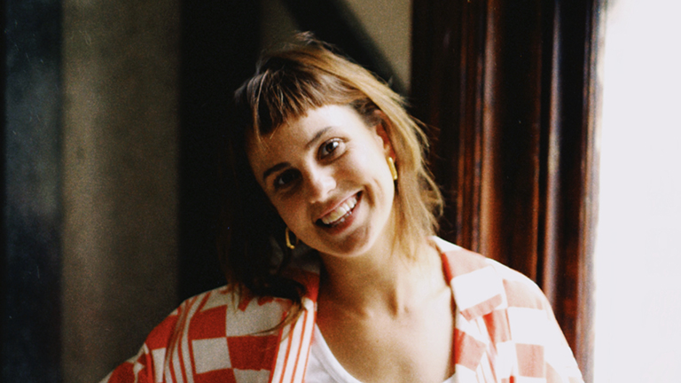 Headshot of Kaylene Langford standing beside a window. Her head is to the side and she is smiling.